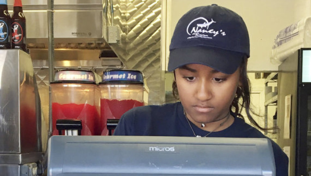 In this Wednesday, Aug. 3, 2016 photo Sasha Obama, daughter of President Barack Obama, works the register at Nancy's Restaurant in Oak Bluffs, Mass., on the island of Martha's Vineyard. (Boston Herald, Christopher Evans via AP)